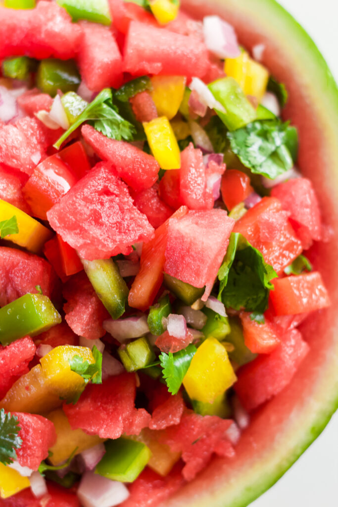 close up of fresh garden salsa recipe with watermelon, green pepper, yellow pepper, red pepper and cilantro